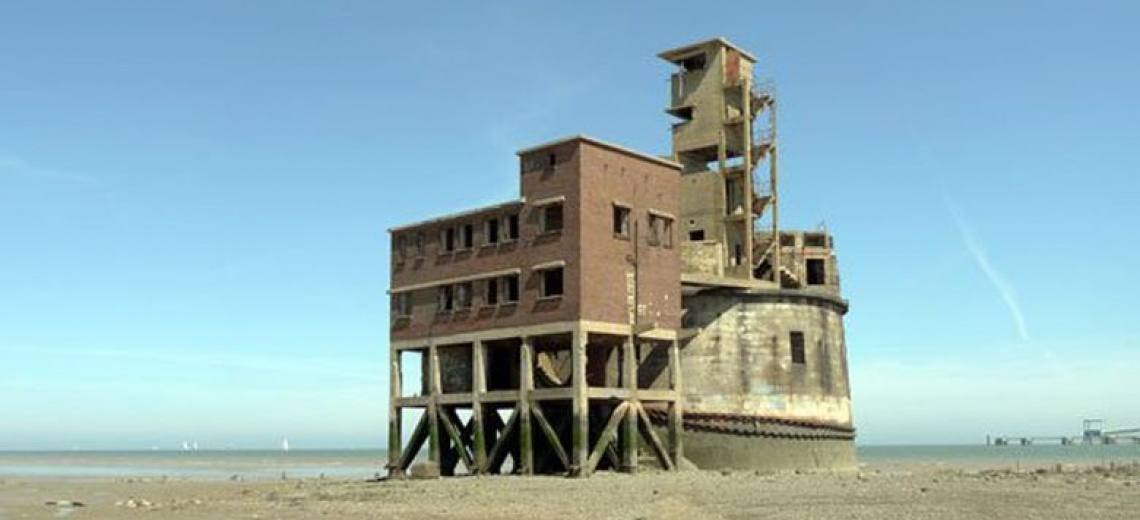 An isolated industrial fort like building on a flat coastal site.