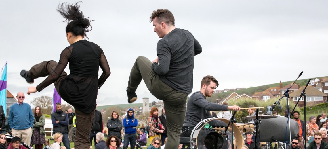 A man and a woman dancing in the open air in front of a small crowd. There is a man playing a drum kit in the background.