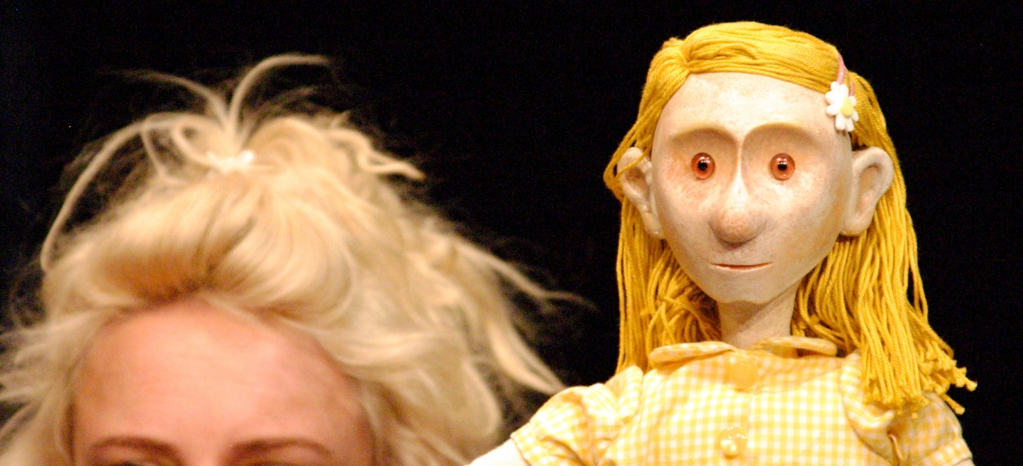 A puppet with yellow hair and dress next to a performer with blond hair.