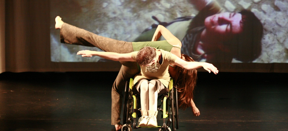 Two performers on a stage, one is in a wheelchair and the other is standing on one leg behind.
