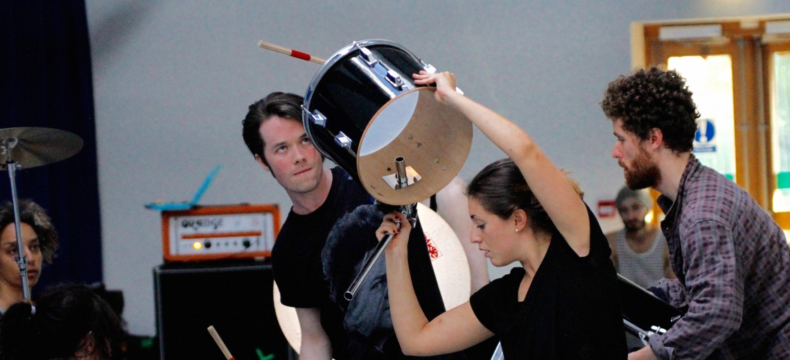 Five people in a room, one holding a drum in the air.