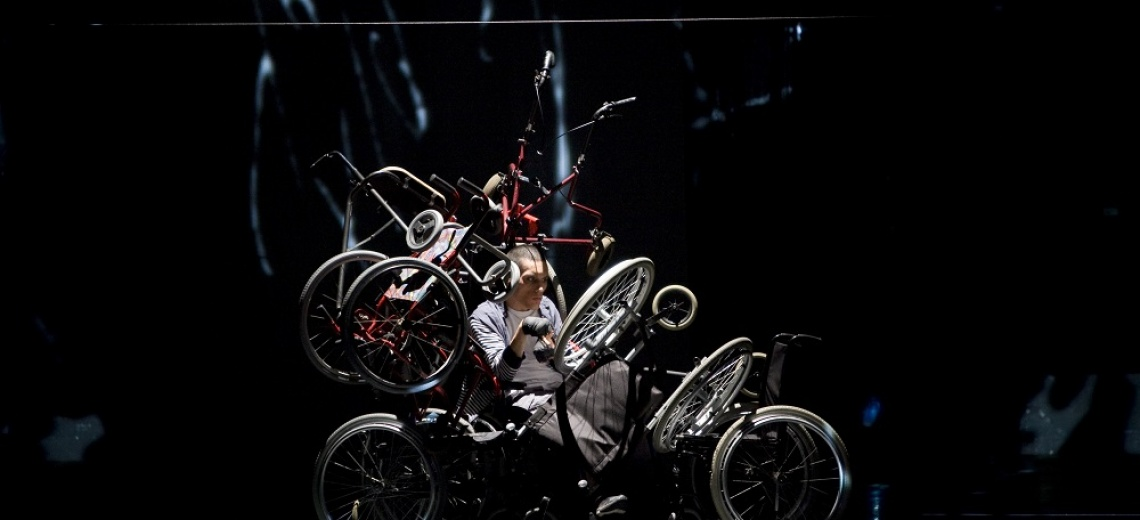 A man on a stage who is positioned under a tangle of wheels and metal frames.