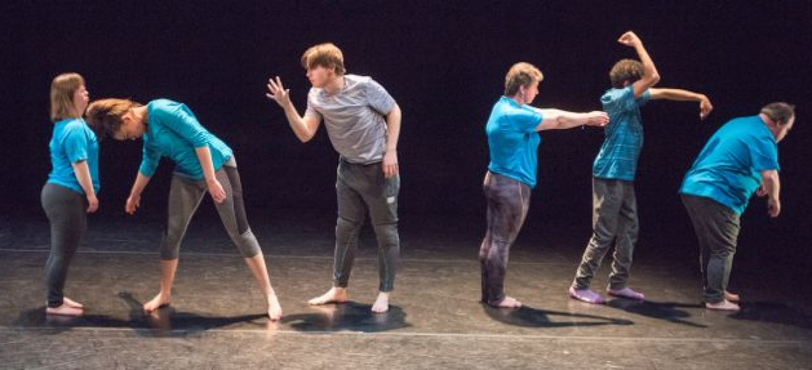 Six performers on a stage in a row, in a range of poses.