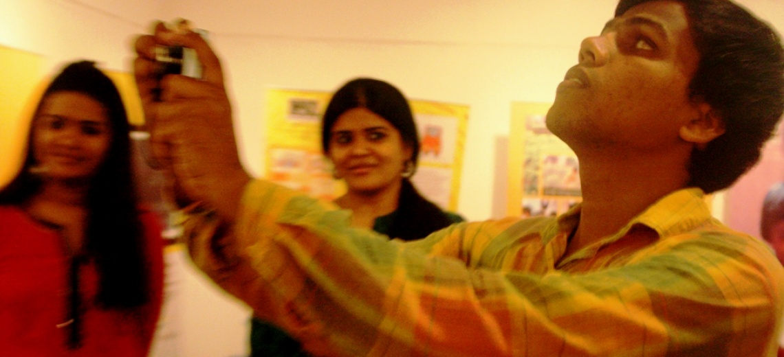 Man holding up a camera to take a photograph. Two women in the background looking at him.