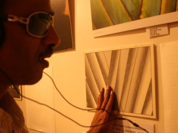 Close up of the face of a man wearing dark glasses and headphones, his hand is feeling a picture on the wall in front of him