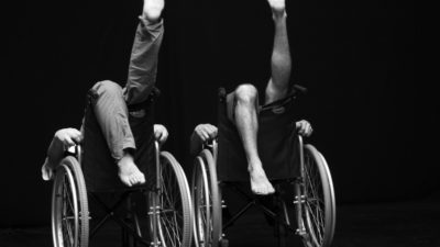 Two people sitting back to front in wheelchairs with their legs in the air.