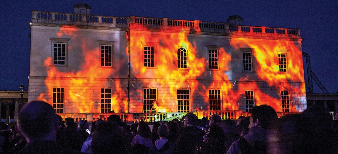 Light projection of fire onto a large stately building.