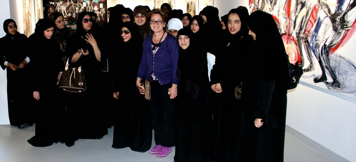 A woman in western clothing standing amongst a group of women in black Islamic dress.