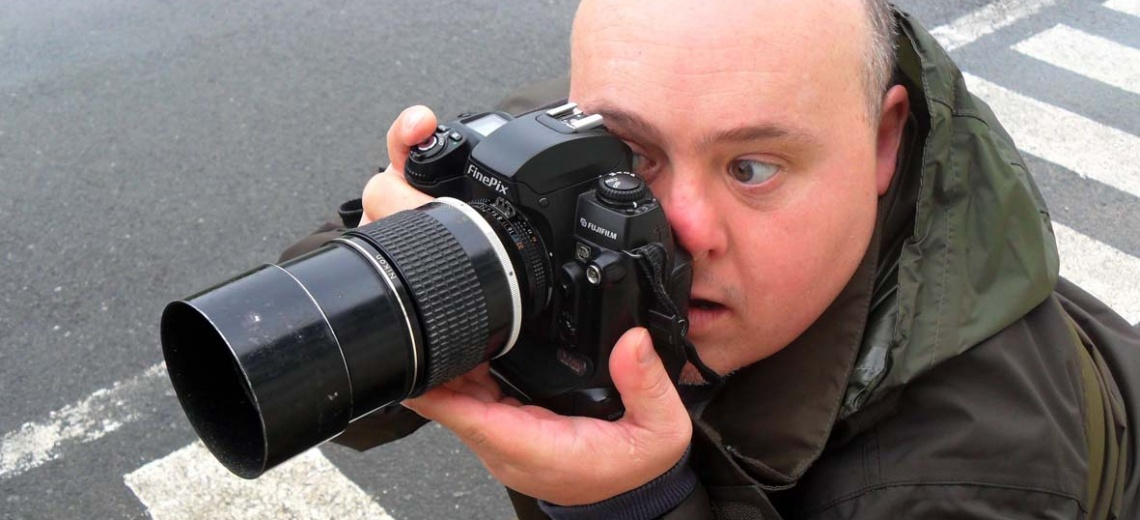 A man holding a long lens camera to his face taking a photograph
