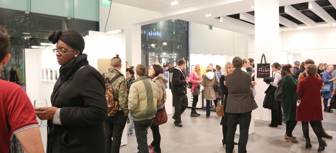 People walking around a white walled gallery
