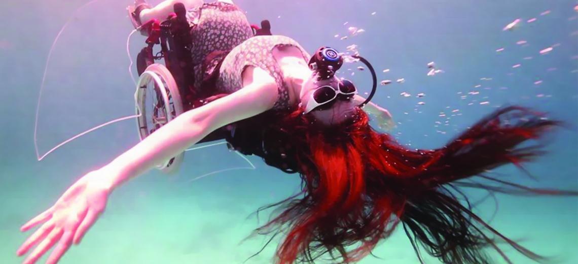 Sue Austin in an underwater wheelchair flipped upside down