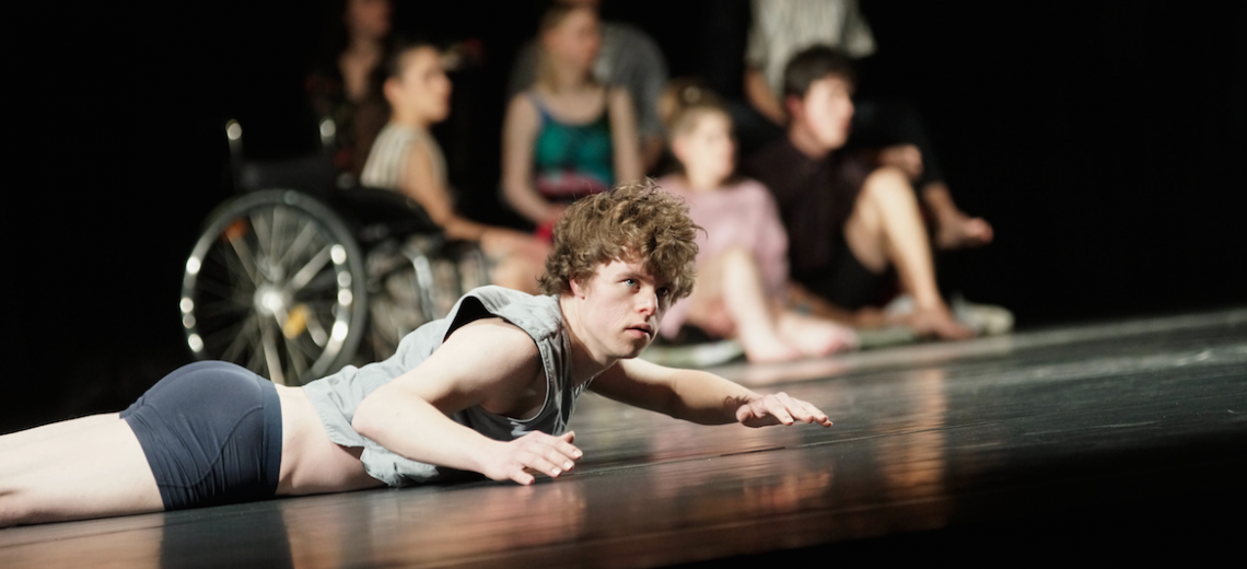 Performer lying on his front on a stage