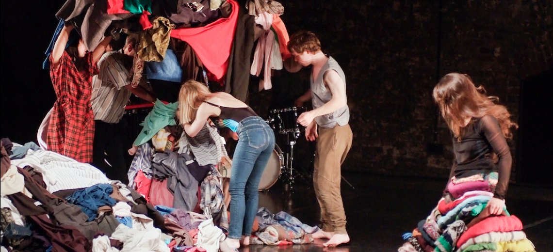 Performers sort through a huge pile of clothes