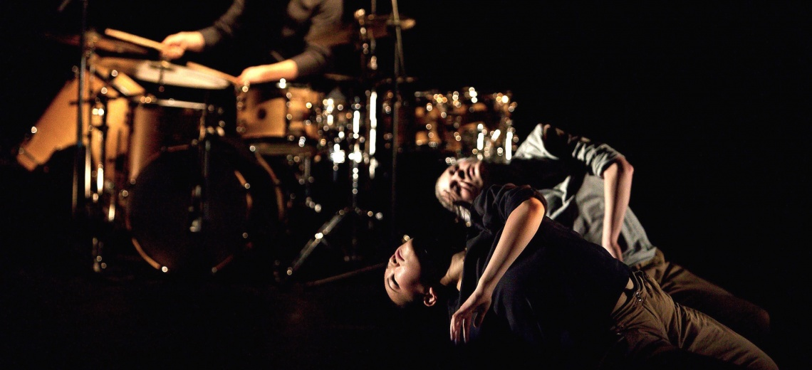 Two people in the foreground lying almost horizontal with their eyes closed. A drum kit is in the background.