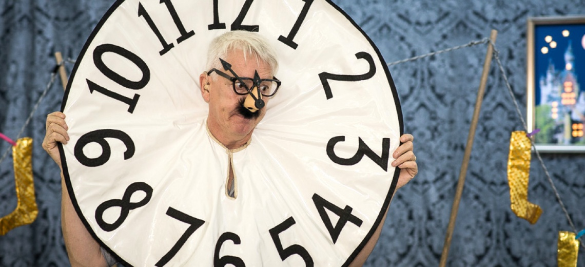 A man with his head pushed through a fabric clock face.