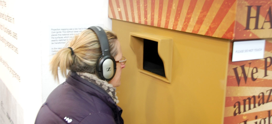 A woman wearing headphones looking into a yellow box.