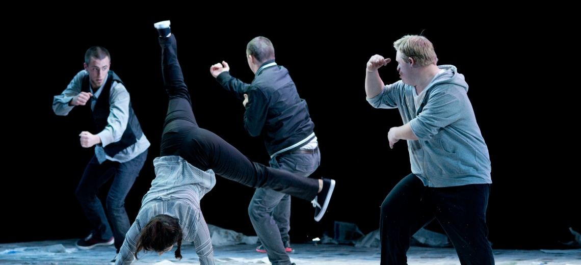Four performers on stage, one is doing a cartwheel.