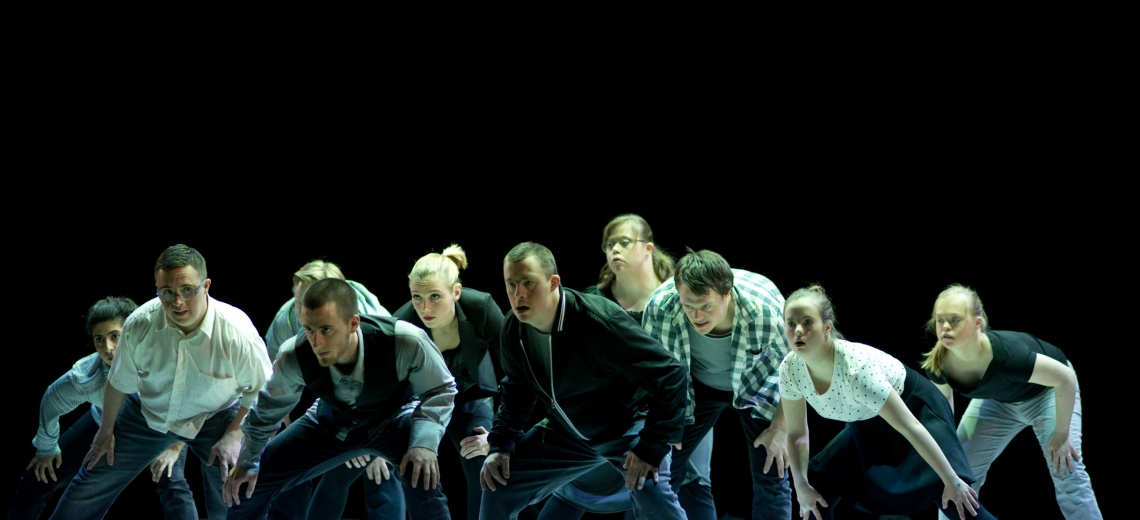 A group of 10 performers on a stage all leaning forwards in the same direction.