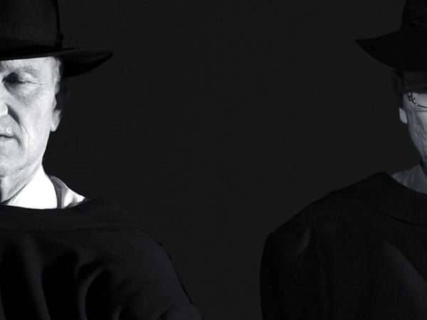 Two men wearing trilby hats, their faces highlighted against a dark background.