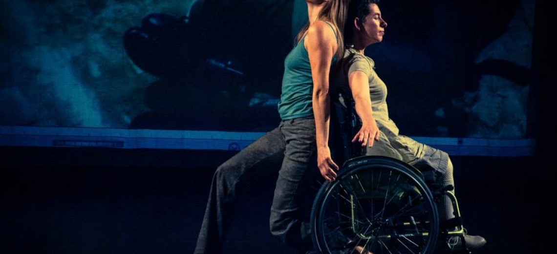 Two women on a stage. One is in a wheelchair.