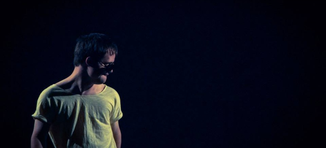 A man in a tee-shirt and dark glasses on a dark stage.