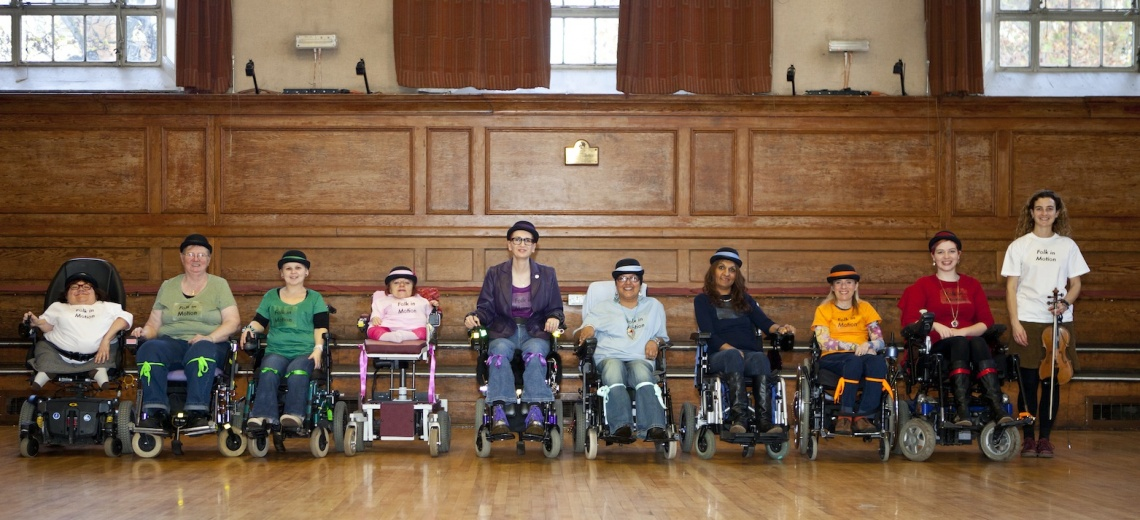 Ten performers in wheelchairs, in a long row wearing bowler hats.