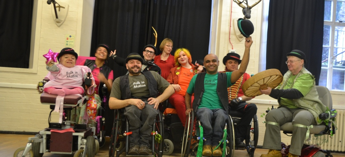 A group of performers in wheelchairs, smiling.