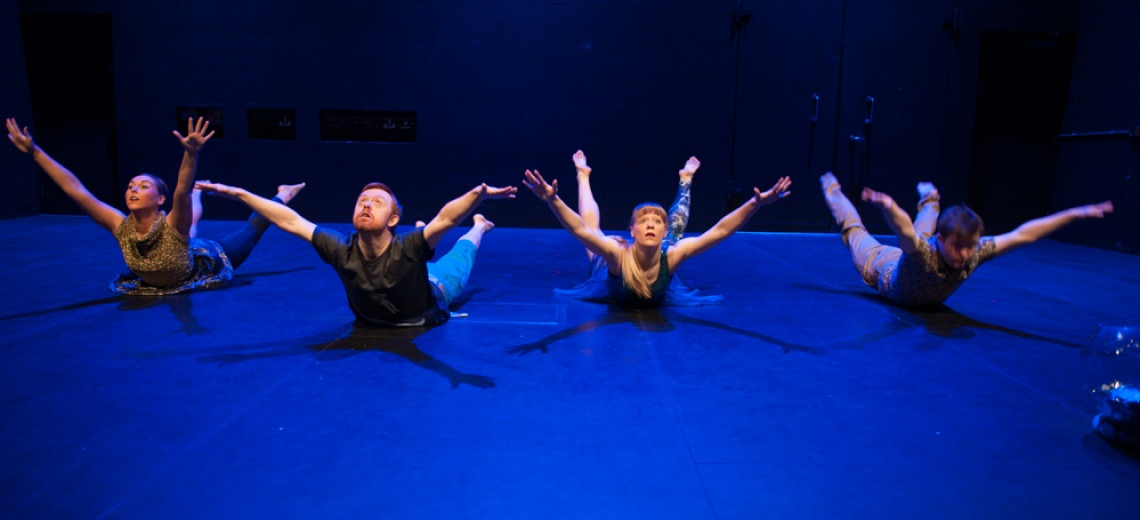 Four performers on a stage all lying on their front with heads, arms and legs raised in the air.