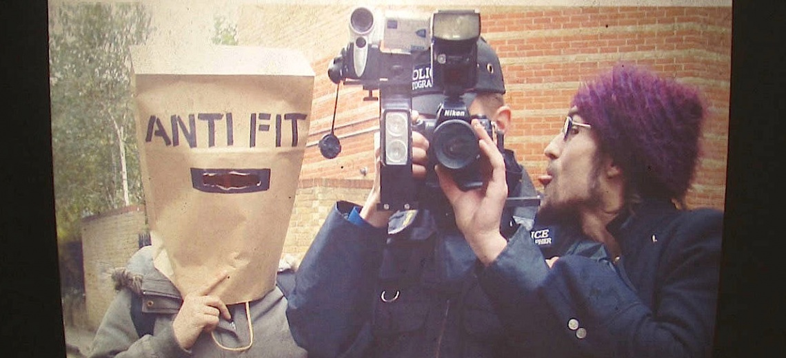Person with camera, 1 sticking tongue and and 1 with paper bag on their head