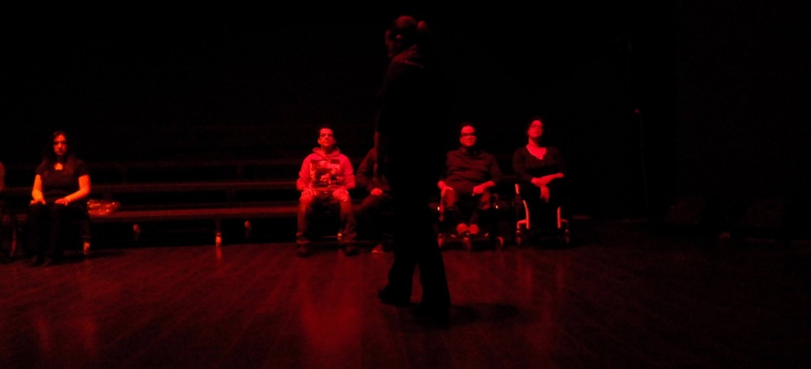 5 seated performers, whilst one paces, cast in red light