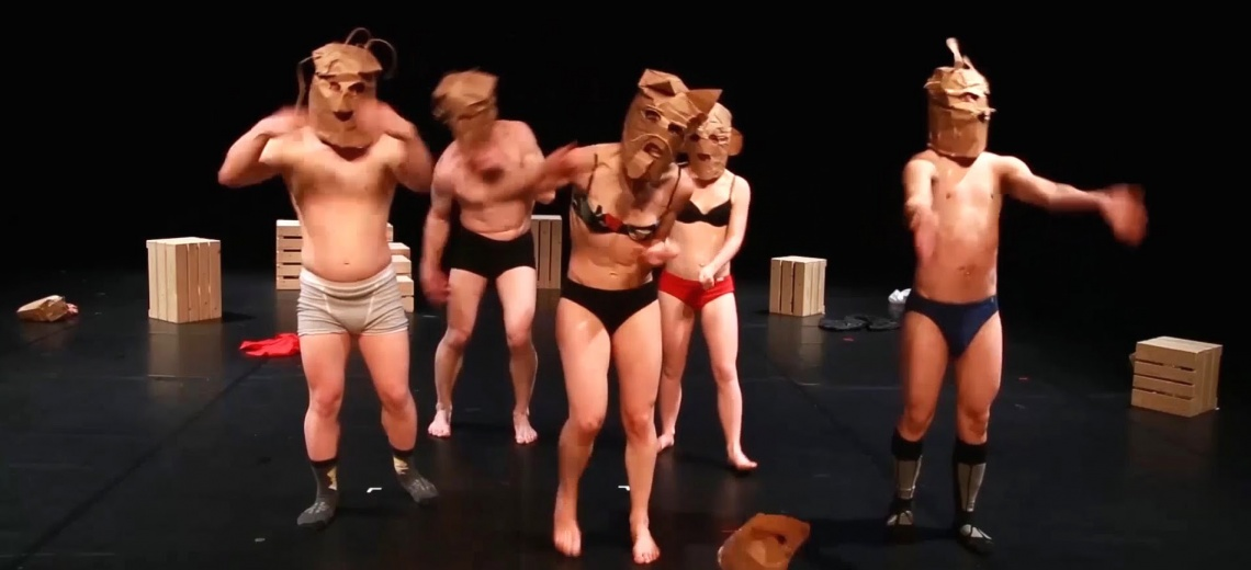 Three men and two women on a stage wearing underwear and a paper bag on their heads.