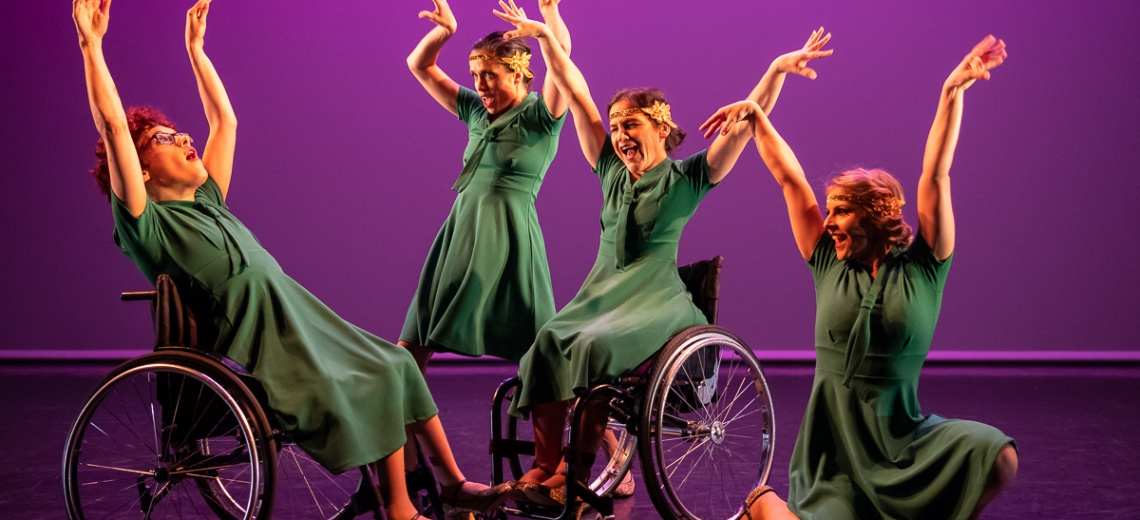 4 dancers, two of them wheelchair users all in same green dress