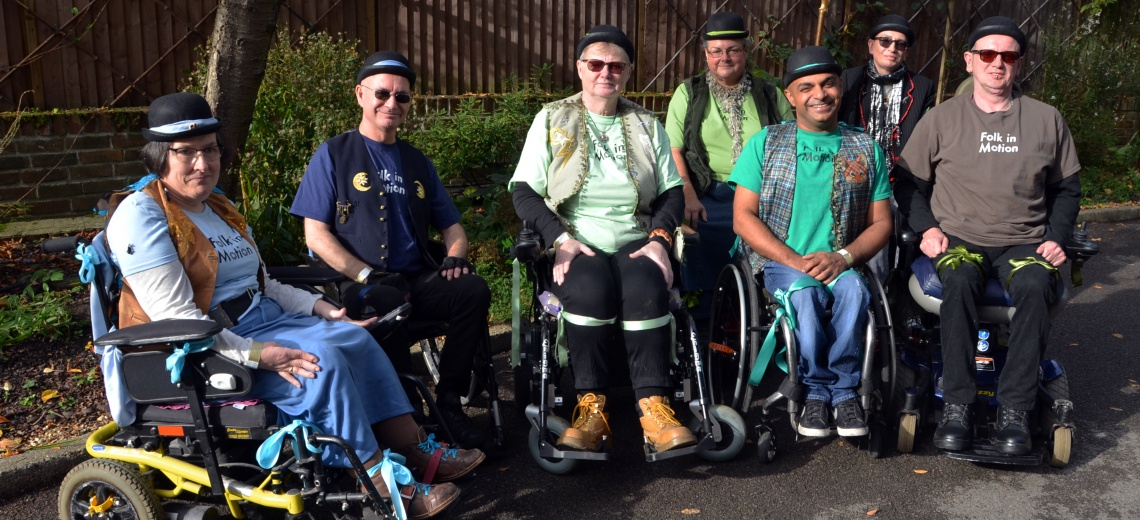 Seven performers in wheelchairs, wearing bowler hats, in a garden setting.