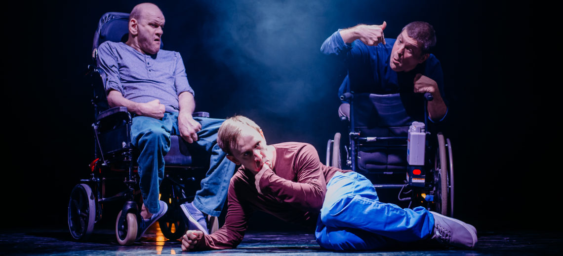 Three men on a stage, one is lying on the floor with his back to the others.