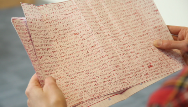 A piece of old-looking paper with incomprehensible letters