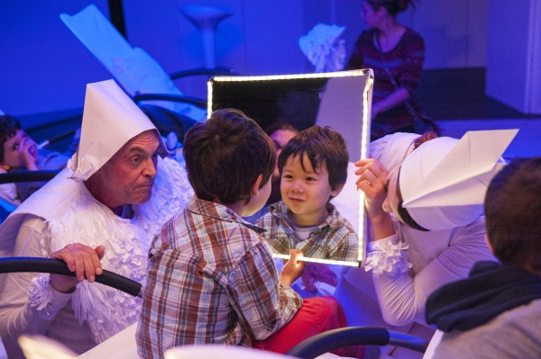 A child looks into an illuminated mirror