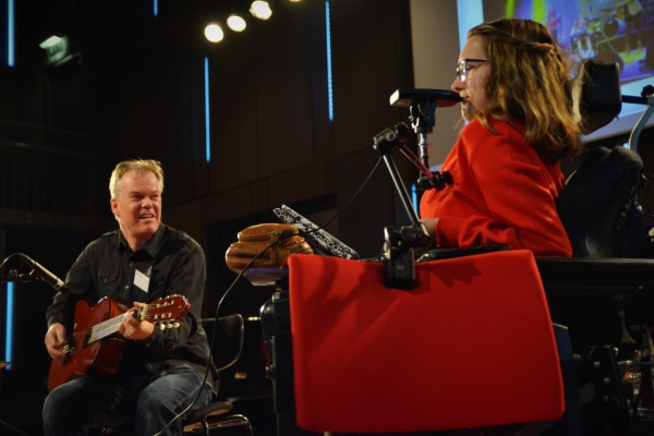 A wheelchair user plays a specially adapted instrument with her mouth