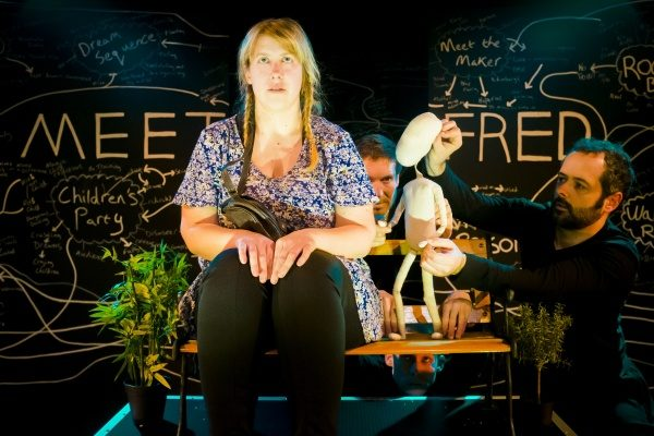 Woman sitting next to banraku puppet