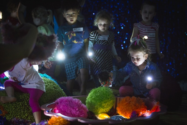 Group of children with torches explore a set