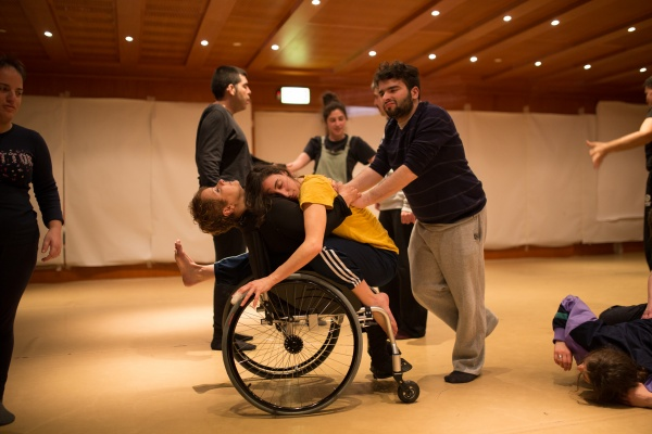 Photograph of a dance workshop featuring disabled dancers, one dancer is hugging another dancer in a wheelchair