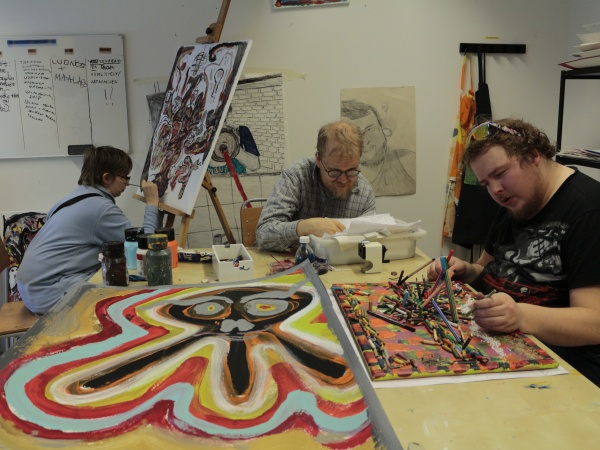 Three artists work closely on painting in a small studio
