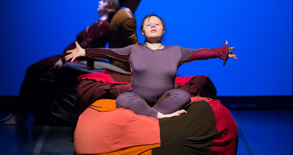 A performer sitting on a large beanbag with her arms outstretched.