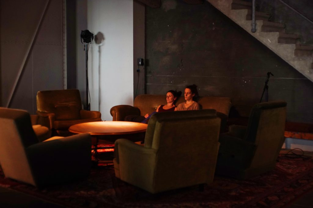 Two female dancers sit back on a dimly lit sofa, their eyes looking ahead, the scene with a rouge glow