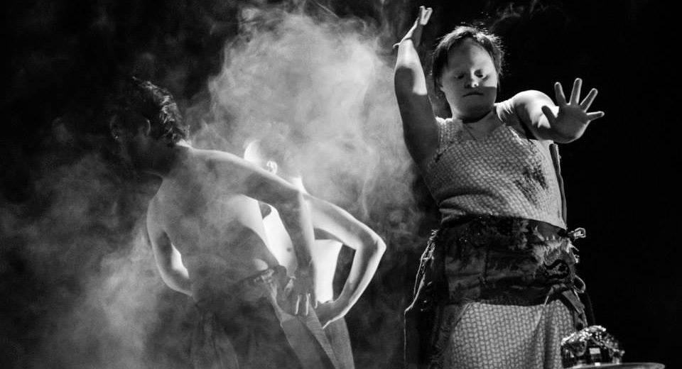 Three dancers on a stage with smoke rising from the background.