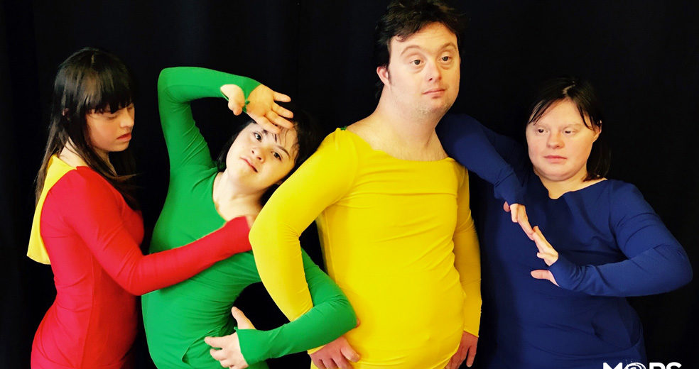 Four dancers in standing a row in brightly coloured leotards.