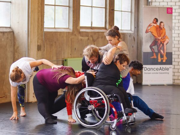 Dancers create a complex group structure reaching forward and backwards together