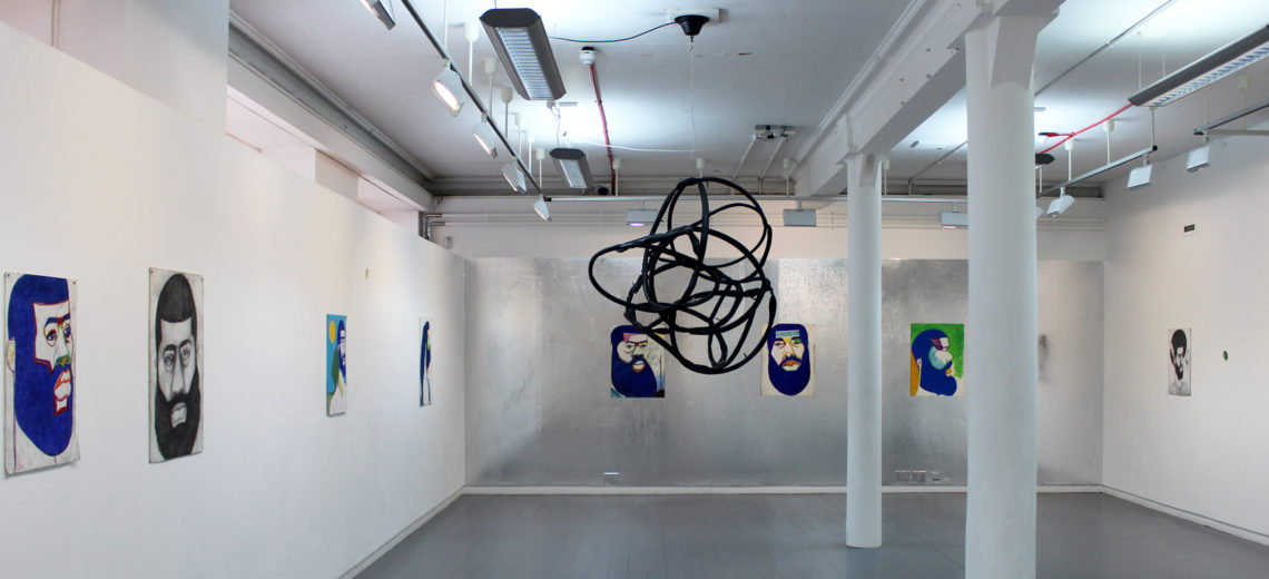 A black twisted cord suspended from the ceiling of an industrial white room with portraits on the walls.