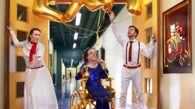 Liz Carr in a golden wheelchair with balloons spelling exit above her