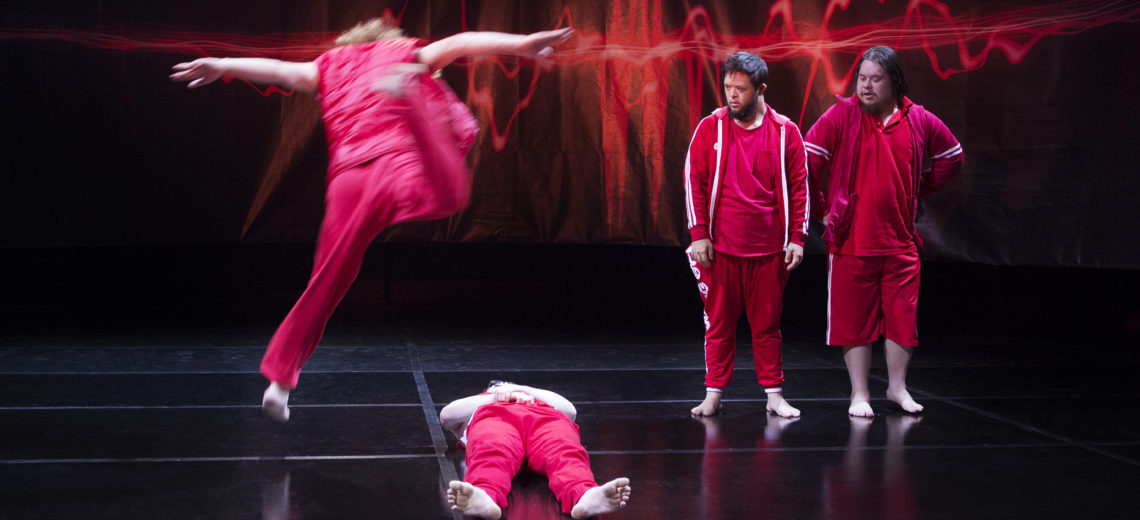 Four performers on a stage, all wearing red clothing.