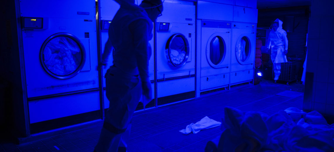 Two performers suspended from the ceiling in a launderette setting.
